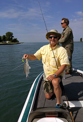 Angler volunteer Bill Wood fishes with Michigan State Senator Geoff Hansen who shows off a white bass he caught.